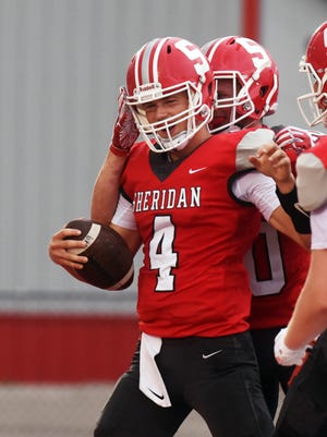 Sheridan senior Josh O'Ryan, left, is met by teammates after scoring a touchdown on Friday night at Paul Culver Jr. Stadium. The game was postponed in the second quarter and resumed on Saturday due to storms in the area.