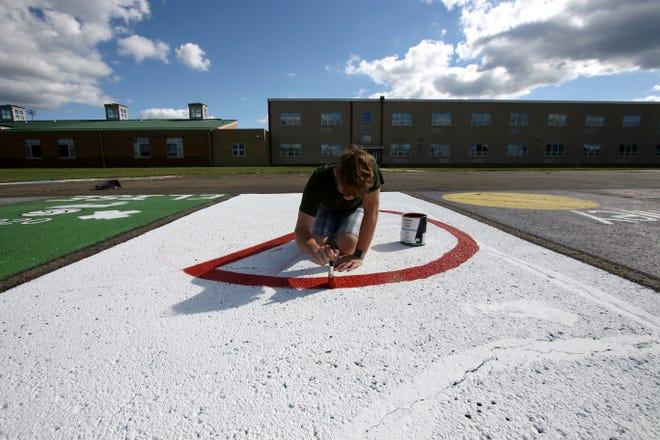 "West Branch senior Joseph Sprague paints a ""do not park"" sign Sunday on his parking spot at West Branch High School."