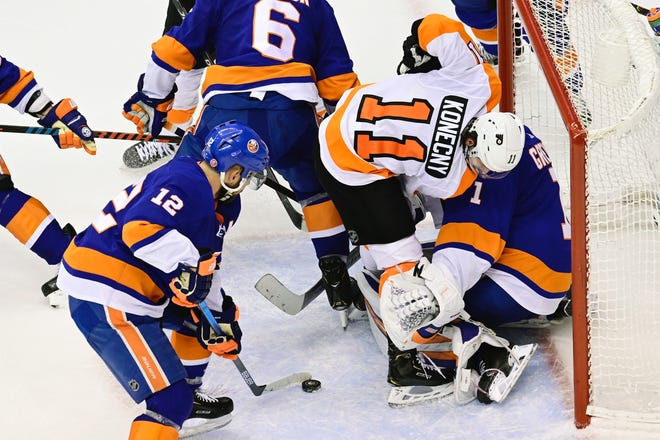 The Flyers' Travis Konecny, 11, collides with Islanders goaltender Thomas Greiss as New York's Josh Bailey, 12, secures the loose puck during Game 4 on Sunday night.