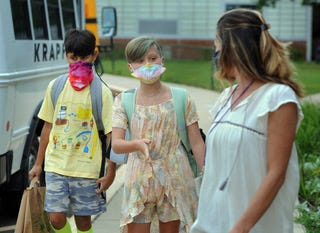 From left, Kade Yerrapathruni and Emma Wirth chat with teacher Alissa Corboy as students arrive for the first day of classes Monday at Tinicum Elementary School in Tinicum Township. (WILLIAM THOMAS CAIN / PHOTOJOURNALIST)