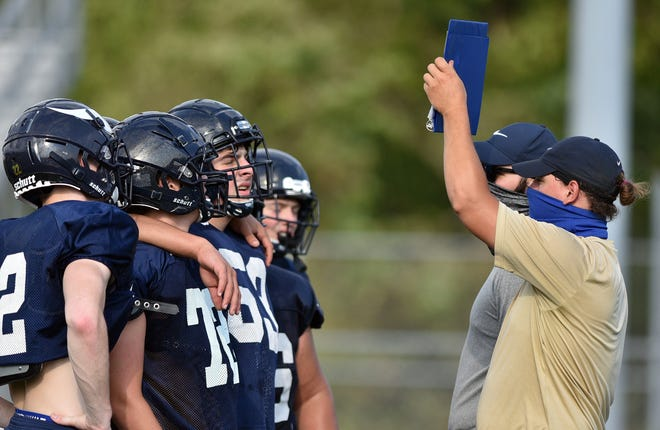 Hopewell High School assistant football coaches hold up the clipboard to the defense during practice Aug. 27.