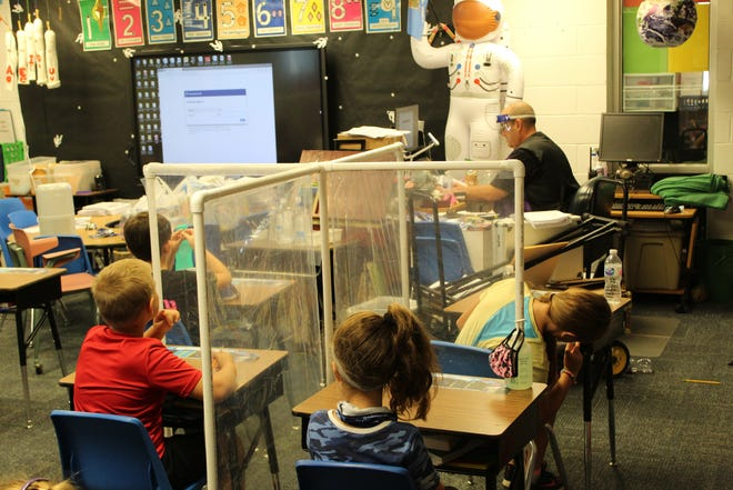 Teacher Jeff Cauthen calls the roll for members of his second-grade 'space station' at Ranch Heights Elementary School.