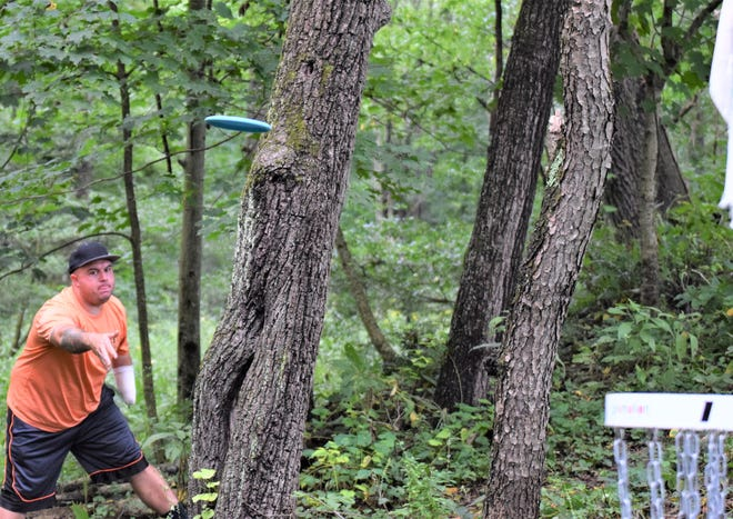 Dustin Alcorn of Massillon shoots his disc at the basket hole No. 1 at Deer Run Disc Golf Course tournament on Saturday in Millersburg. Alcorn posted the winning score with a 109.