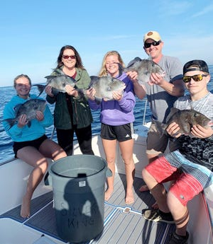 This group of anglers from Iowa show off some of the triggerfish they caught on March 16 while fishing aboard the Silver King with Capt. Alex Hare.