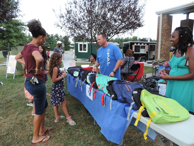 Master Cpl. Brian Gedney, school resource officer at William Henry Middle School, hands out backpacks at a community event last fall. School resource officers fall under the same branch of service as community policing in the Dover Police Department.