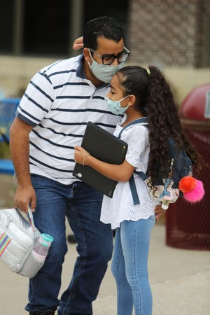 In this file photo, Karma Abdelmalak, 9, a fourth-grader, gets a hug and a kiss from her father, Magdy, Aug. 31, 2020, as he drops her off for the first day of the 2020-21 school year for Burlington School District students at North Hill Elementary School. The district began last school year with a mask mandate in place for students and staff before Iowa Gov. Kim Reynolds, with just weeks before the end of the school year for most districts, signed a law prohibiting school boards from enforcing mask mandates. On Monday, federal judge issued an order temporarily blocking that law. Since then, Burlington and West Burlington school boards, along with several others throughout the state, have reimplemented mask mandates.
