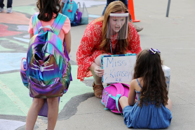 North Hill Elementary SchoolKindergarten teacher Kya Kimsey greets students as they wait in line on the playground before heading into the school building for the first day of school Monday for Burlington School District students.