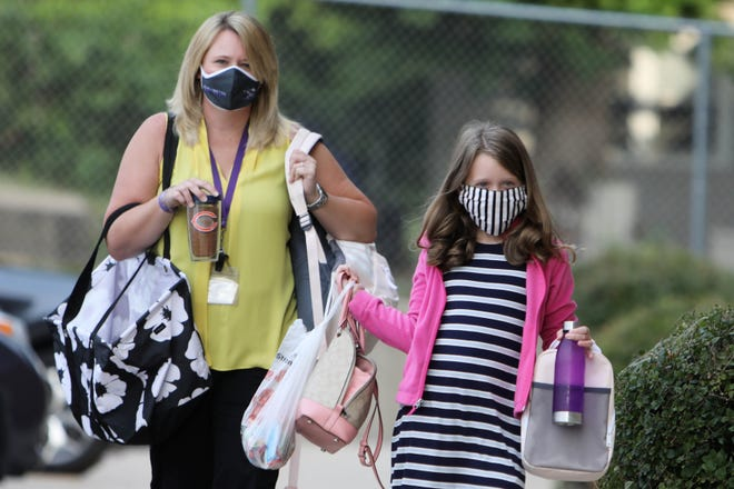 Aubree Mason, 8, a third grade student accompanies her mother Kellie, a 4th grade teacher, as they arrive Monday for the first day of school at North Hill Elementary School.