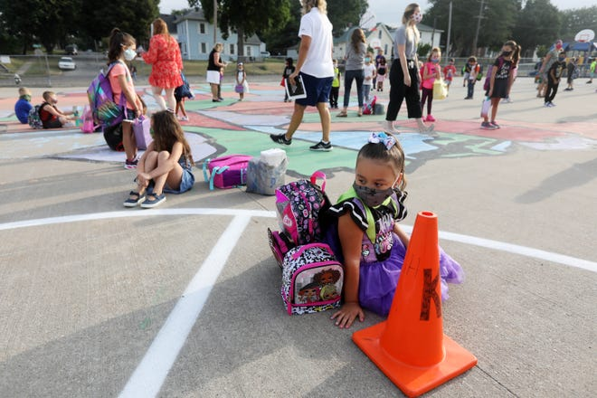 Lupe Marshall, 5, a kindergarten student, waits in line on the playground Monday before the  first day of school for Burlington School District students at North Hill Elementary School.
