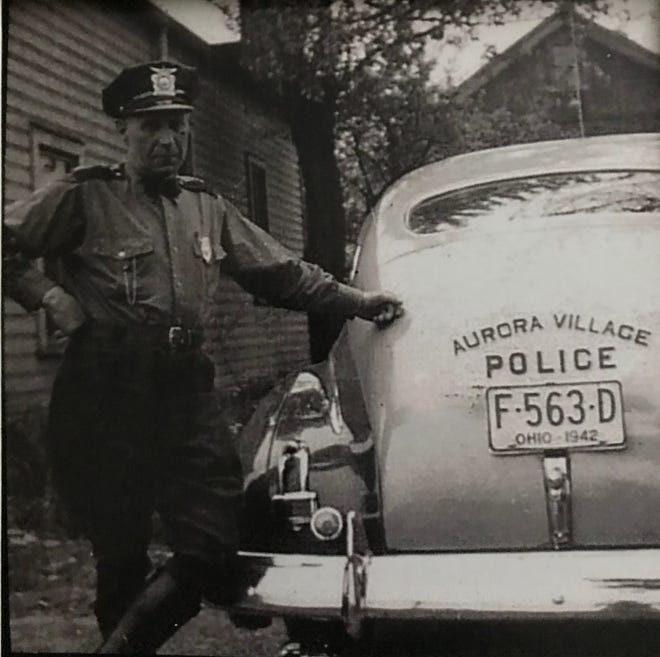 Art Hall standing by his car that he provided to perform his duties. He followed Sam Miller as township constable and retired in 1958.
