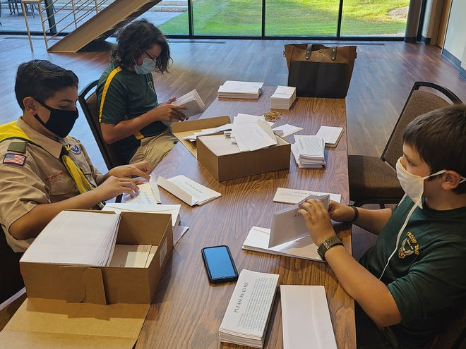 Grant Courtnage, Matthew Packard, and Rokko Szarell help stuff Aurora One Fund pledge cards into envelopes Aug. 20 at Our Lady of Perpetual Help Parish. The annual charity fundraiser began last week.