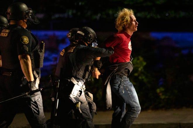 Police make arrests at the scene of nightly protests in Portland, Oregon.