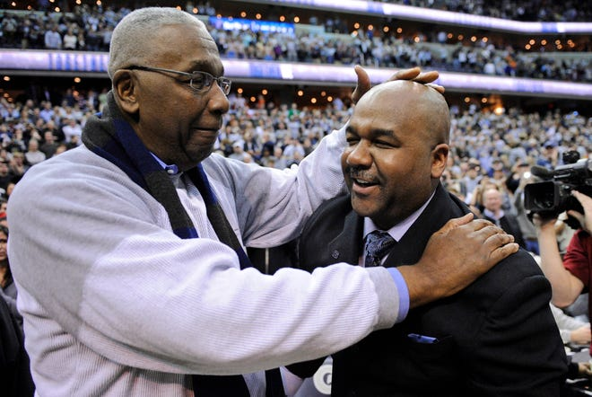 "Former Georgetown coach John Thompson Jr., left, congratulates his son Georgetown head coach John Thompson III, right, after the Hoya's 61-39 win over Syracuse in an NCAA college basketball game in Washington in March 2013. Thompson Jr., the imposing Hall of Famer who turned Georgetown into a ""Hoya Paranoia"" powerhouse and became the first Black coach to lead a team to the NCAA men's basketball championship, has died. He was 78. His death was announced in a family statement Monday. No details were disclosed."