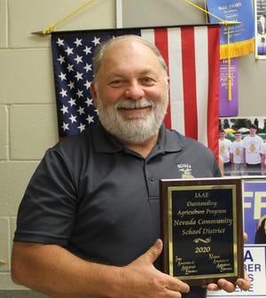 A plaque is awarded to Nevada agricultural educator Kevin Cooper by the Iowa Association Agricultural Educators.