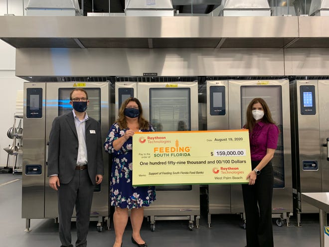 From left, Justin Long, Mary Anne Cannon and Sari Vatske pose with a $159,000 check presented by Raytheon Technologies to Feeding South Florida. The money will go toward providing food assistance amid the coronavirus pandemic.