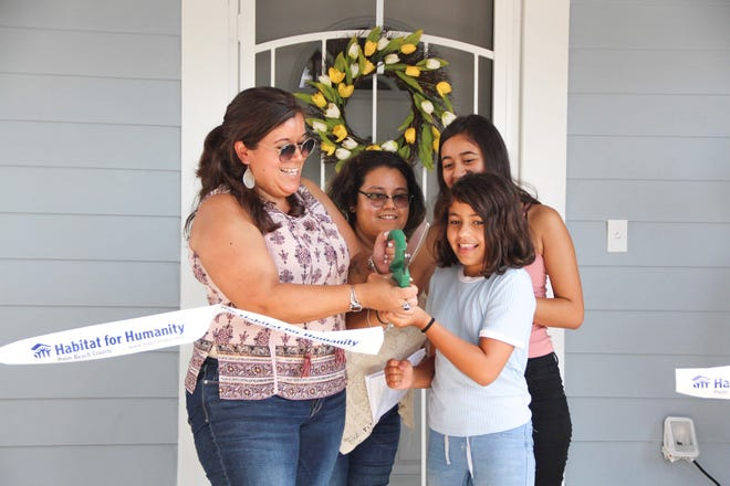 A Palm Beach County family celebrates their newly built Habitat for Humanity home with a ribbon cutting. Habitat homes are sold to partner families at no profit, and are financed with affordable, zero-interest loans.