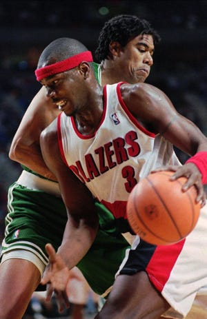 "FILE - In this Dec. 27, 1995, file photo, Portland Trail Blazers forward Cliff Robinson, front, drives on Boston Celtics' Pervis Ellison during NBA action in Portland, Ore. Former Trail Blazer Robinson says he is recovering from a ""minor brain hemorrhage."" Last week Robinson's family disclosed that the 50-year-old former forward was being treated at Providence St. Vincent Medical Center. Robinson issued a statement on Tuesday, March 14, 2017, saying he's in the ""process of getting better."" (AP Photo/Don Ryan, File)"