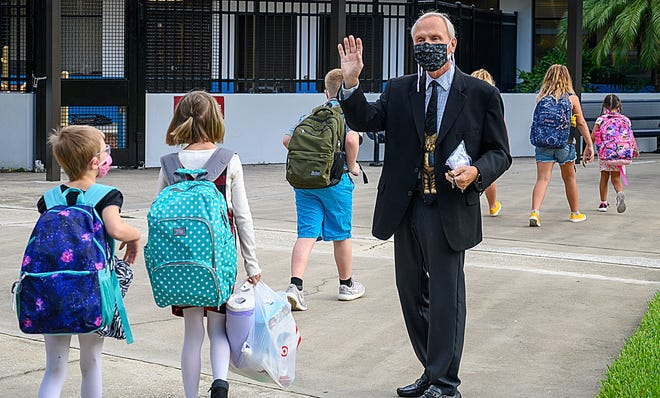 W. D. Hartley Elementary School principal Dr. Paul Goricki welcomes students back to school on the first day of school on Monday.