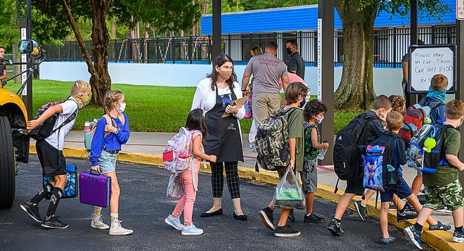 W. D. Hartley Elementary School staff member Rachel McKenny watches as students arrive for the first day of school on Monday.
