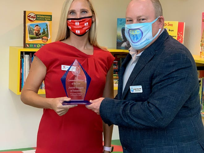 Melissa Hembree, JLS president, accepting the award from Douglas Stanley, CPC executive director