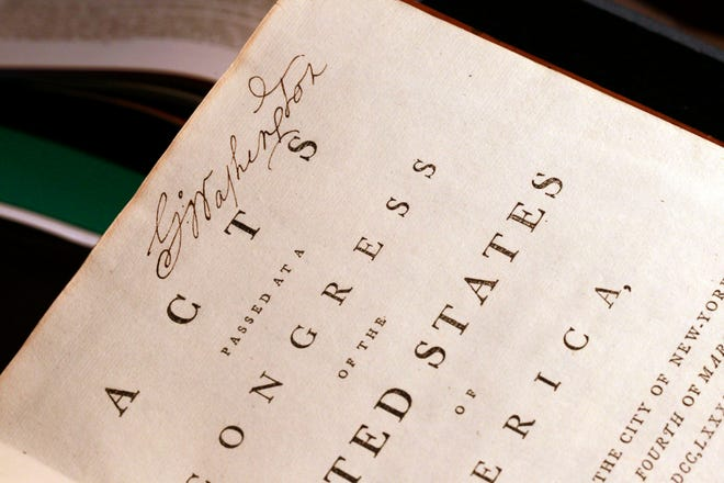 George Washington's signature is seen on a personal copy of the acts of the first Congress (1789), containing the U.S. Constitution and the proposed Bill of Rights.