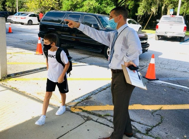 Fort Clarke Middle School Principal Jared Taber directs a masked student as he makes his way onto the campus Monday morning. Monday was the first day of school for thousands of K-12 public school students, as well as students at the University of Florida and Santa Fe College. [Brad McClenny/Gainesville Sun]