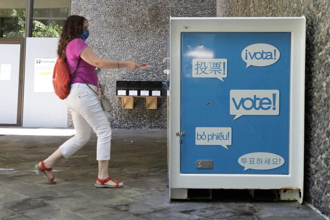 A person puts their ballot for Washington state's primary election at a drop box in Seattle. [AP Photo/Ted S. Warren, File]