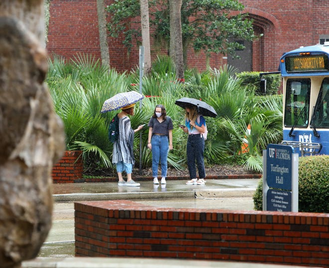 Students wait in the rain for a bus at the University of Florida as the first day of classes begin at the school in Gainesville on Aug. 31. UF earned the No. 6 spot in the 2021 U.S. News & World Report rankings. U.S. News & World Report assessed more than 1,400 colleges and universities on 17 indicators of academic standards. The data in the rankings applied to student and faculty cohorts that precede the COVID-19 pandemic.