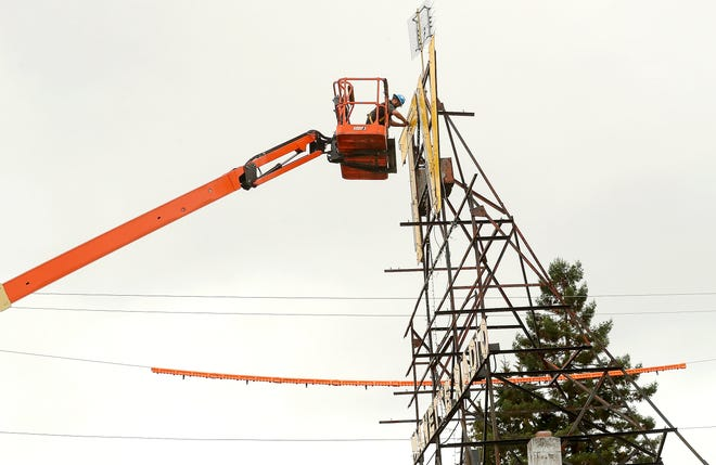The neon tubing is dismantled as Hanson Signs prepares to remove the iconic Manette TV sign on Monday.