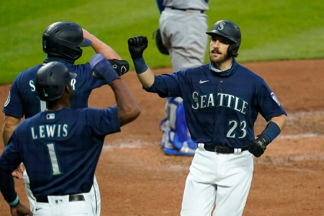 Seattle Mariners' Austin Nola (23) is greeted at home on his three-run home run by Kyle Lewis (1) and Kyle Seager during the third inning of a baseball game against the Los Angeles Dodgers on Wednesday, Aug. 19, 2020, in Seattle.