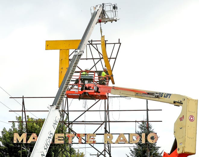 "Crew members from Hanson Signs remove the remaining part of the ""V"" as the iconic Manette TV sign is taken down on Monday. The sign will be renovated and the owner of the building intends to have it returned to its original location."