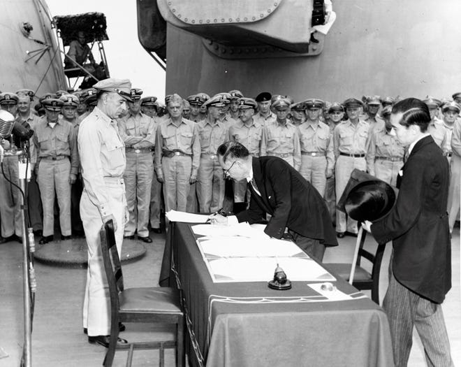 Japanese Foreign Minister Mamoru Shigemitsu signs the Instrument of Surrender on behalf of the Japanese Government, on board USS Missouri (BB-63), 2 September 1945. Lieutenant General Richard K. Sutherland, U.S. Army, watches from the opposite side of the table. Foreign Ministry representative Toshikazu Kase is assisting Mr. Shigemitsu.