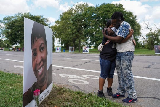 """Delano Sparks of Detroit is comforted by his sister Jamie Cook of a Detroit as they get out of their car at a photo of their mother Asturd Sparks on display as part of photos of Detroit residents and people with connections to Detroit who died during the pandemic during the Memorial Drive on Belle Isle in Detroit on Monday, August 31, 2020.""""Driving through it was a lot to sink in because you realize that you're nor the only person that's hurt. Looking at all of these pictures and stuff make you realize that it's a lot of people that were truly affected by this. This for me just means that we all just need to band together, vote and just make everybody as happy as you can while you're here on this earth. We can be gone in five minutes. I know for a fact. I talked to my mom. It was the first time she ever told me she was scared when she was in the hospital,"""" Delano Sparks of Detroit said about losing his mother on April 14, 2020. Sparks said he wasn't let into the hospital at the time in April to see his mother. """"This is hard. This is the hardest thing I've ever been through in my life. It still hits me like it was yesterday and it's been months."""""""