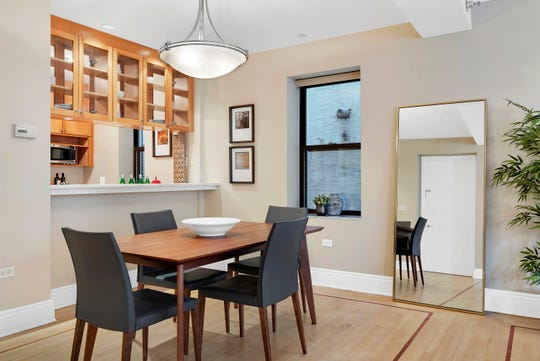 A wood table that seats four, is used to help define a dining area as opposed to overwhelm.
