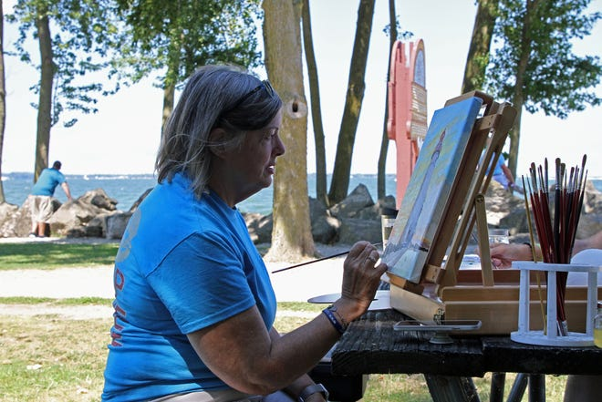 Lin Wilson, a realism artist from Marblehead, works on the fourth in a series of the four seasons at the Marblehead lighthouse.