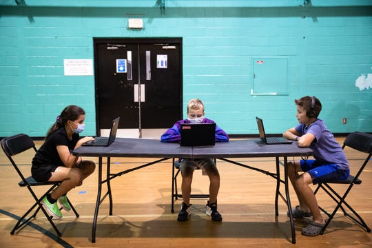Miranda Lluberes, 9, a fifth grade student, Jacob Kephart, 10, a fourth grade student, and Ethan Rains, 10, a fifth grade student, all work on laptops at the Eastside Family YMCA in Taylors, Monday, August 31, 2020.
