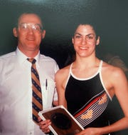 Iowa swimmer Vickie Nauman poses with her coach Peter Kennedy while holding a plaque she received for a second-place finish at the Big Ten Conference meet in 1984. Nauman, a Des Moines native now living in Los Angeles, is part of a large contingent of former Hawkeyes organizing an effort to try to save the swimming and diving program from extinction.