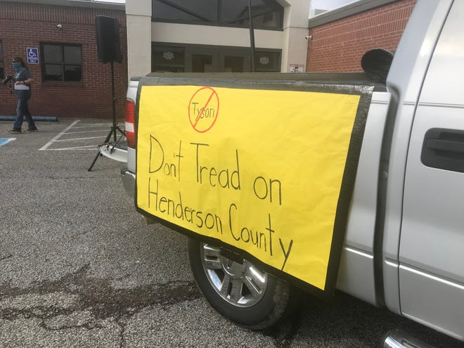 A sign hangs off the side of a pickup truck at a gathering of citizens against Tyson Foods in Henderson County.