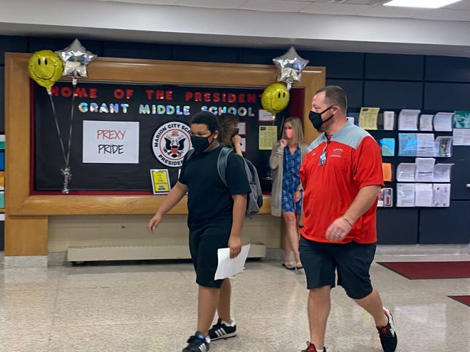 A teacher guides a student to his class on the first day of school at Grant Middle School Monday, August 31, 2020.