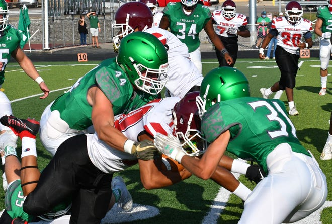 New Castle's Matt Bell (No. 44) and Jace Logston (No. 31) make a tackle during a game against Tindley at New Castle High School Saturday, Aug. 29, 2020.