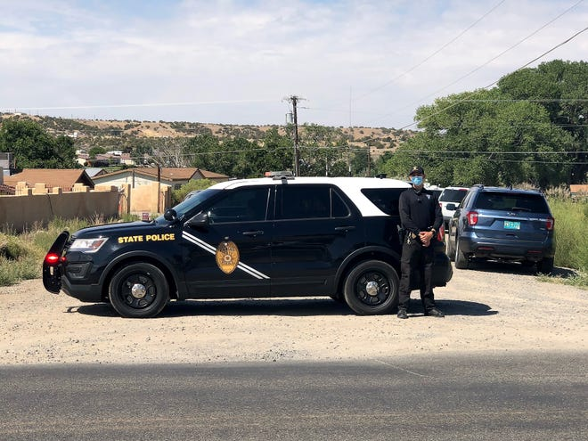 A New Mexico State Police officer blocks traffic on County Road 3177 as an investigation into an officer-involved shooting takes place on the morning of Aug. 31 in the Crouch Mesa area.