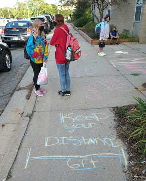 Muir student prepare to re-enter their school for the first time since mid-March. The school chalked welcoming words, and social distancing reminders, on the sidewalk.
