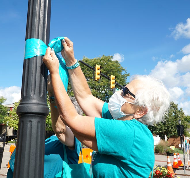 Terrie Karebian helps to tie a teal ribbon around a lamp post along Main Street in Northville on Aug. 31, 2020 to raise awareness of ovarian cancer.