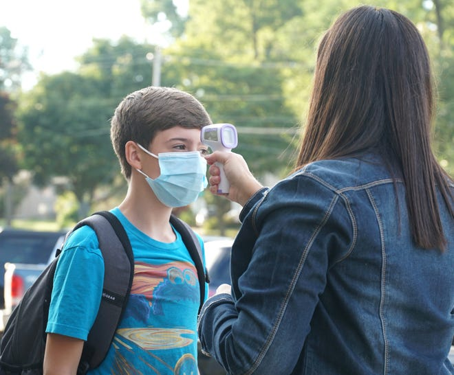 Atticus Ray gets his temperature checked before entering Muir Middle School on Aug. 31, 2020.