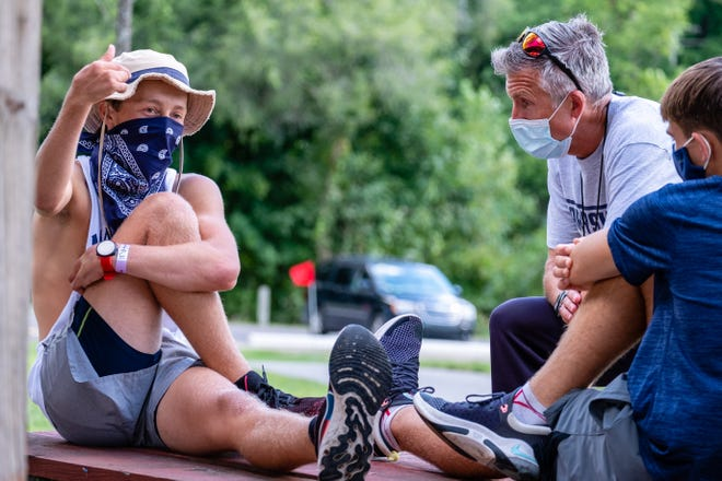 Marysville High School cross country coach Steve Rogers, second from right, talks with junior runner Brock DenUyl after competing in the Skipper Early Bird Invite Monday, Aug. 31, 2020, at Marysville Municipal Park.