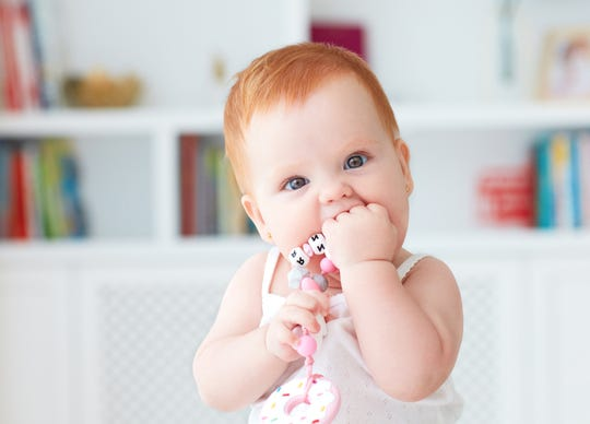 A baby girl biting a silicone nibbler toy