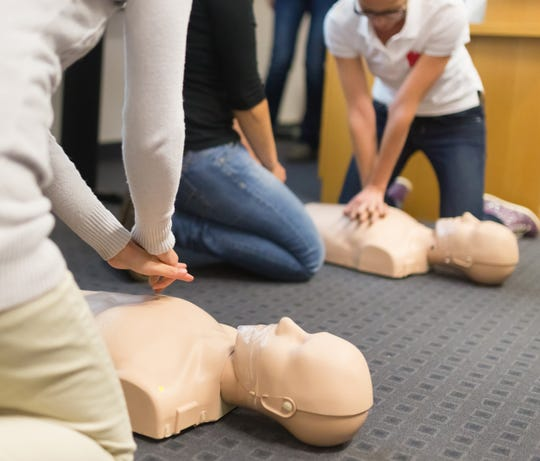 A group of adult education students practice CPR chest compression on a mannequin.