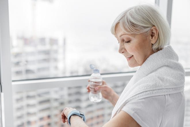 There are several ways to ensure you're getting what you need out of your exercise. Here, a woman uses a watch to check her heart rate. Other devices will check steps taken and chart the time you've spent working out.