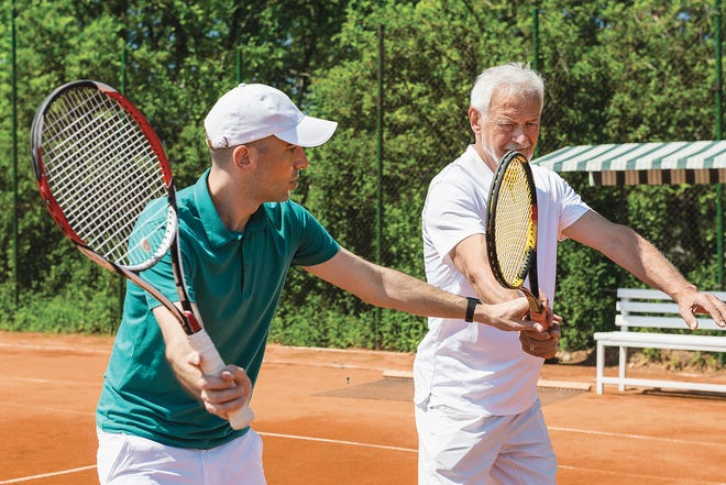 A tennis instructor works on volleying with a senior adult student.