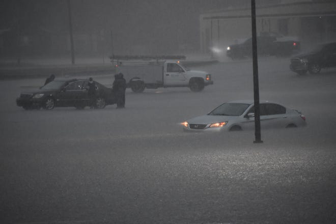 A car is stranded in flood waters behind a shopping center on South Commerce Street on Tuesday.